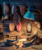Shoemaker workshop with tools, shoes and leather. On old wooden table stock photos