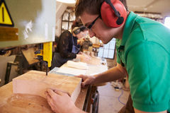 Shoemakers cutting and shaping wood to make shoe lasts Stock Photography
