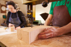 Shoemakers cutting and shaping wood to make shoe lasts Royalty Free Stock Photo