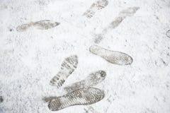Shoeprints fotspår, bootprintd på jordning coved vid vit snö Royaltyfria Foton