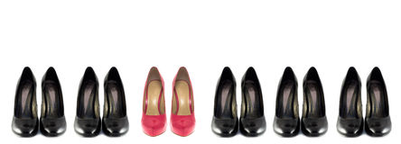 Shoes. Some black classic and one pair pink unusual shoes on the white background stock photos