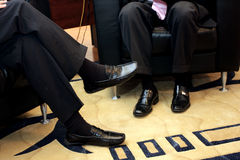 Shoes. Tow mans sitting on a chair, shoe detail Stock Images