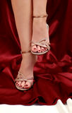 Shoes. Woman legs in small shoes with heels on red satin Royalty Free Stock Photos