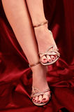 Shoes. Woman legs in small shoes with heels on red satin Stock Image