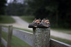 Shoes. On the fence with blurred road on the background Royalty Free Stock Photos
