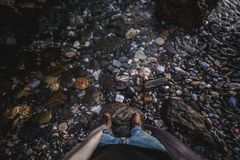 Shoes from above on rock with water royalty free stock images