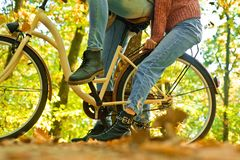 Shoes for active lifestyle. Unrecognizable couple with bike in autumn forest. Romantic couple on date. Date and love royalty free stock photo