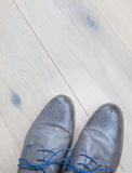 Shoes against a wooden floor Stock Images