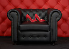 Shoes on the armchair. Pair of red women`s shoes with rhinestone on black leather armchair. Red leather carriage upholstery on the background Royalty Free Stock Image