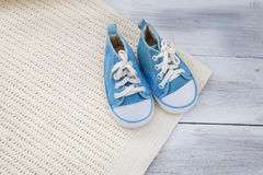 Shoes for a baby boy and a blanket on a  wooden background. Stock Photo