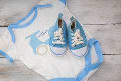 Shoes for the baby and clothing for a boy on a white wooden bac Stock Image