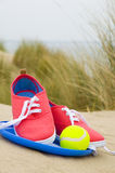 Shoes, ball and frisbee on beach. Shoes, ball and frisbee in sand dunes on beach Royalty Free Stock Photo
