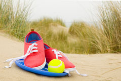 Shoes, ball and frisbee on beach landscape. Shoes, ball and frisbee in sand dunes on beach landscape Royalty Free Stock Photo