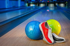 Shoes and balls for bowling game. Shoes and balls for bowling on the background of the playing field Royalty Free Stock Photography