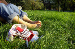 Shoes and bare feet on grass. View of girl's legs and her bare feet on grass next to pair of athletic shoes. Face of girl not in photo Stock Images