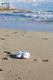 Shoes on the beach. White gym shoes on an ocean coast Royalty Free Stock Photos
