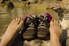 Shoes on the beach. Shoes and bare feet on the beach royalty free stock images
