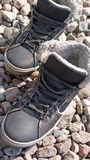 Shoes on the beach stones Stock Photography