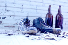 Shoes and bottles. Vintage shoes and beer bottles with a background old wall Royalty Free Stock Image