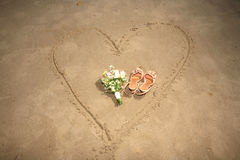 Shoes and bouquet on a heart. Made on sand Royalty Free Stock Photos