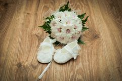 Shoes and bouquet on a wooden floor Royalty Free Stock Photography