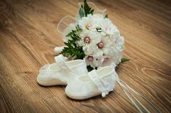 Shoes and bouquet on a wooden floor Royalty Free Stock Images