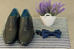 Shoes and bow-tie near vase on tablecloth Royalty Free Stock Photo