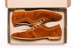 Shoes in a box. Suede classic shoes in a box on a white background Royalty Free Stock Photo