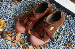 Shoes boy scout brown on ground gravel. Classic old brown shoes boy scout Royalty Free Stock Image