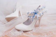 Shoes for the bride and bridal garter. High-heeled ivory wedding shoes and lace garter, selective focus Stock Images