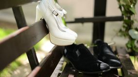 Shoes of bride and groom on a wedding day on the bench