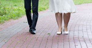 Shoes of a bride and groom walking Stock Photos