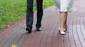Shoes of a bride and groom walking Royalty Free Stock Photos