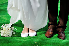 Shoes the bride and groom with wedding bouquet, newlyweds are re Royalty Free Stock Photography