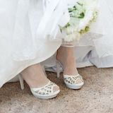 Shoes of bride under wedding dress Royalty Free Stock Image