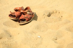 Shoes. Brown leather sandals on a sandy beach. Summertime. Royalty Free Stock Photography