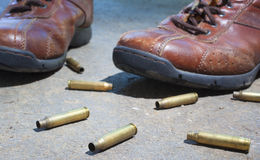 Shoes and bullets Stock Photography