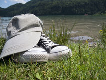 Shoes and cap by the lake Royalty Free Stock Images