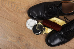Shoes and cleaning equipment on a wooden floor Stock Photography