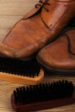 Shoes and cleaning equipment on a wooden floor Royalty Free Stock Images