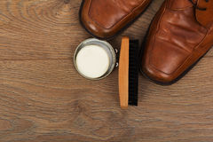 Shoes and cleaning equipment on a wooden floor Royalty Free Stock Photos