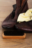 Shoes and cleaning equipment on a wooden floor Royalty Free Stock Photography