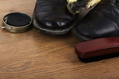 Shoes and cleaning equipment on a wooden floor Royalty Free Stock Image