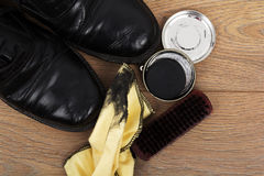 Shoes and cleaning equipment on a wooden floor Royalty Free Stock Photo