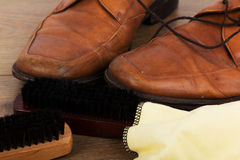 Shoes and cleaning equipment on a wooden floor Stock Images