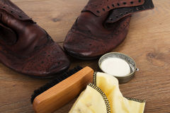 Shoes and cleaning equipment on a wooden floor Stock Image