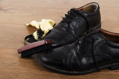 Shoes and cleaning equipment on a wooden floor Stock Photos