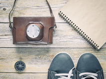 Shoes, compass,notebook  and film camera. On wooden table Stock Image