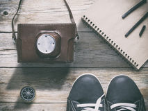 Shoes, compass,notebook and film camera. On wooden table. Traver photography and art concept. Travel artist set royalty free stock photos
