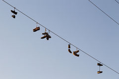 Shoes dangling on a electric cable over the street Royalty Free Stock Photo